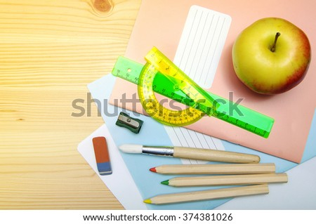 Notebooks, brush, colored pencils, ruler, sharpener, eraser, apple on a wooden surface. School supplies for drawing and the letter - stock photo