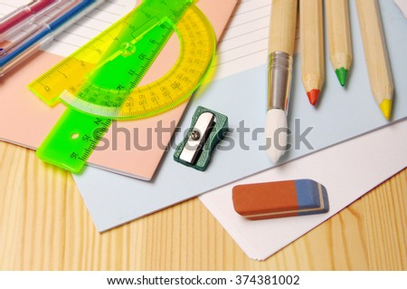 Notebooks, brush, colored pencils, ruler, sharpener, eraser on a wooden surface. School supplies for drawing and the letter - stock photo