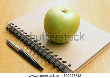 Notebooks, pens and apples
