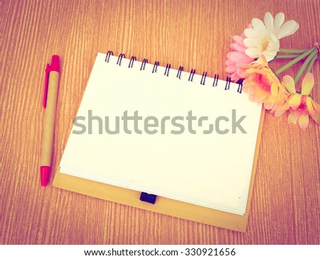 notepad and pen on wooden background ,vintage tone