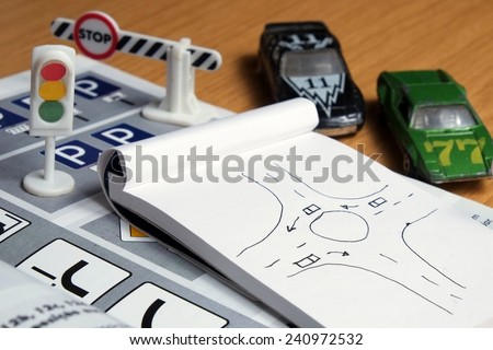 Notepad, book of traffic rules, toy cars, traffic lights and stop sign on a desk table. Studying and preparing for driving test - stock photo