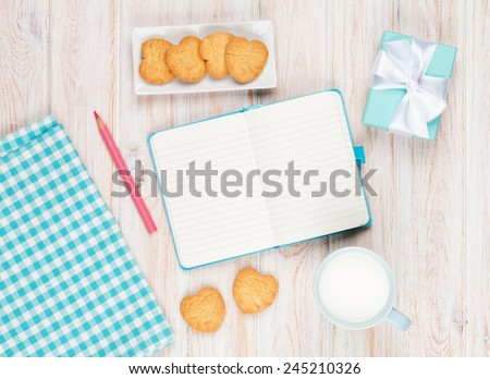 Notepad, cup of milk, heart shaped cookies and gift box on white wooden table - stock photo
