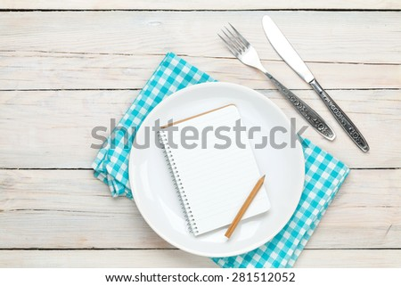 Notepad for recipe over empty plate and silverware on white wooden table background - stock photo