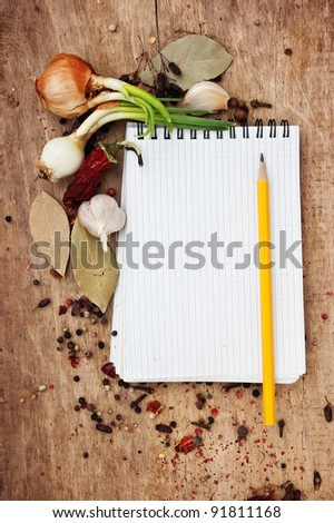 notepad for recipes and spices on an old wooden table - stock photo