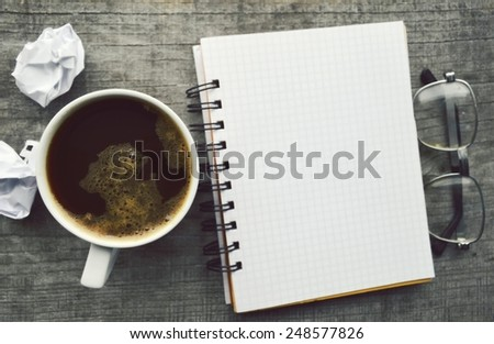 Notepad,reading glasses,hot Cup of coffee on wooden background - stock photo