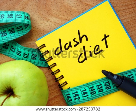 Notepad with dash diet, apple and measure tape - stock photo