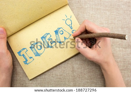 Notepad with hand drawing sketchy Idea word with light bulb  - stock photo