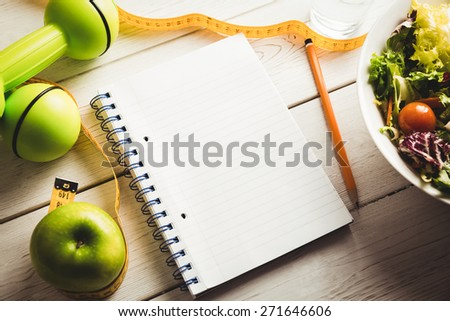 Notepad with indicators of healthy lifestyle on wooden table - stock photo