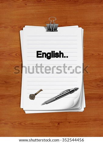 "Notepad with paper clip isolated on a wooden surface. A pen and an old key are on the paper. ""English"" is written on the notepad as a reminder."
