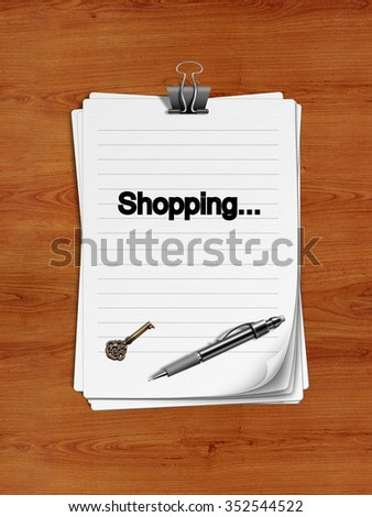 "Notepad with paper clip isolated on a wooden surface. A pen and an old key are on the paper. ""Shopping"" is written on the notepad as a reminder."