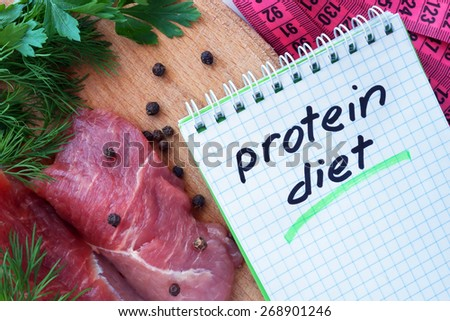 Notepad with protein diet and fresh meat  on wooden board - stock photo