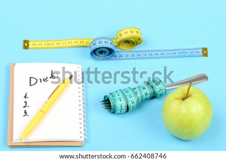Notepad with retractable ballpoint pen on it and written diet plan near measuring tapes, fork and green apple, isolated on turquoise background