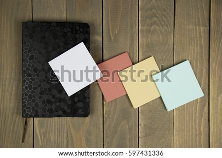 notepad with sticker on wood background