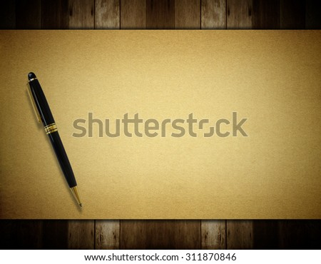 Notepaper and pen on wooden background.