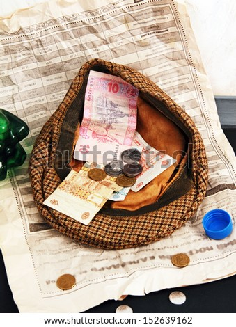 Notes and coins in the cap beggar, newspaper on the sidewalk, empty bottle. - stock photo