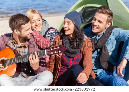 Nothing but friends and guitar. Group of young cheerful people sitting at the riverbank together while young handsome man playing guitar and smiling  - stock photo