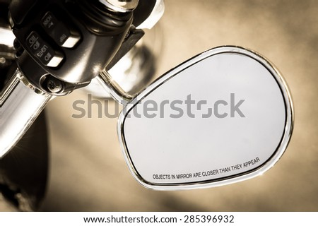"Nothing is as it seems: motorcycle rear-view mirror warning ""objects in mirror are closer than they appear"". - stock photo"