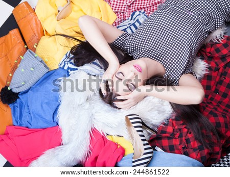 Nothing to wear concept, young attractive woman lying down on a pile of clothes - stock photo
