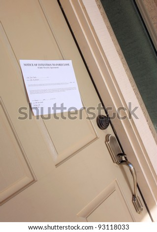 Notice of foreclosure hanging on the front door of a family home. - stock photo