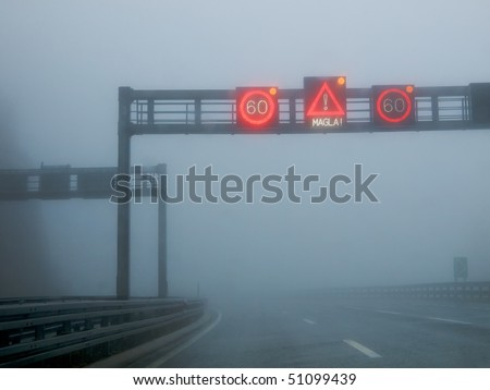 Notification traffic sign on a highway at strong fog - stock photo