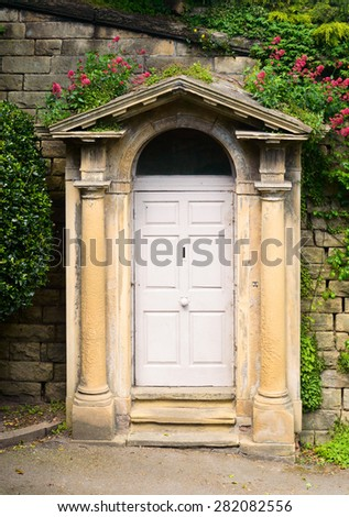 NOTTINGHAM, ENGLAND - MAY 26: A classical style archway, with columns surrounds a door. Situated within the grounds of Nottingham Castle. In Nottingham, England. On 26th May 2015.