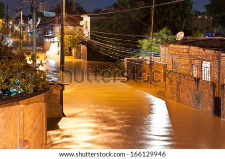 NOVA IGUACU, RIO DE JANEIRO, BRAZIL - DECEMBER 6: Poor living area flooded after heavy rain on 6th December, 2013. The water level of local river got few meters higher, many houses were flooded. - stock photo