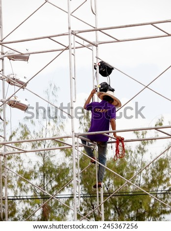 November 6, 2014. Busy unidentified workers climbing high and built metal rod construction outdoor for a music stage performance show for LOY KRATHONG festival in KHON KAEN province, THAILAND