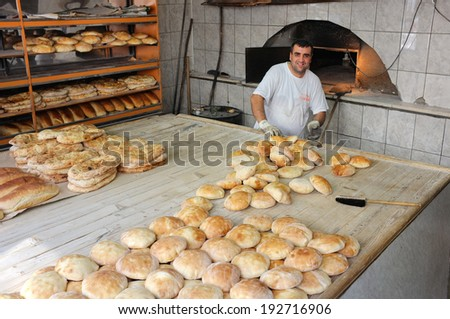 NOVI PAZAR, SERBIA - JULY 26: smiling baker and freshly baked bread in Novi Pazar bakery. Shot in 2013 - stock photo