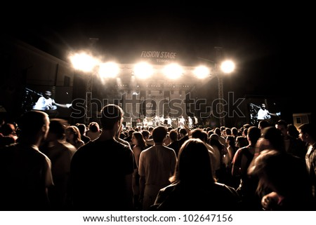 NOVI SAD, SERBIA - JULY 7: Audience infront of the Fusion Stage at EXIT 2011 Music Festival, during Superhiks' performance on July 7, 2011 in the Petrovaradin Fortress in Novi Sad. - stock photo