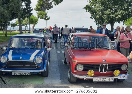 NOVIGRAD, CROATIA - SEPTEMBER 13, 2014: Unrecognizable people look around vintage cars on 5th International Old Timer Car Rally. The event organized by the old timer club Eppur si muove from Umag. - stock photo