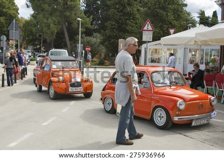 NOVIGRAD, CROATIA - SEPTEMBER 13, 2014: Unrecognizable people watch the parade of vintage cars on 5th International Old Timer Car Rally organized by the old timer club Eppur si muove from Umag. - stock photo