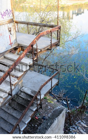 """Novosibirsk, Russia - 24 April 2016: The Word """"Ass"""" written on an abandoned staircase at the lake with a bunch of garbage in Novosibirsk from 24 April 2016. - stock photo"""