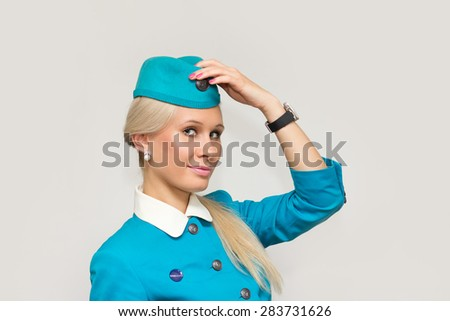NOVOSIBIRSK, RUSSIA - JUNE 26, 2014: S7 Crew member (flight attendant) Dressed In Blue Uniform On Gray Background. S7 is the founding airline of world's 3nd largest airline alliance - Oneworld. - stock photo