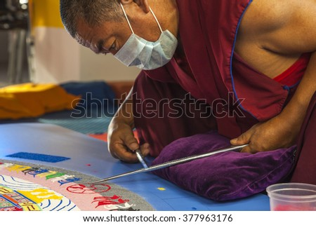NOVOSIBIRSK, Russia - 13 November 2015: Buddhist monk making sand mandala Kalachakra. Mandala - is a spiritual and ritual symbol in Hinduism and Buddhism, representing the Universe. - stock photo