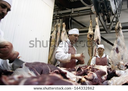 NOVOSIBIRSK, RUSSIA - SEPTEMBER 6, 2011: Butchers chopping meat with cleaver, cut up carcasses of beef in Novosibirsk, Russia - stock photo
