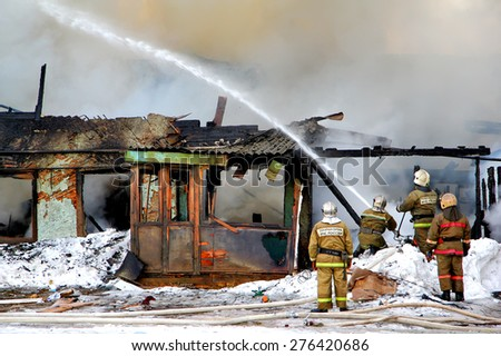 NOVYY URENGOY, RUSSIA - MAY 9, 2015: Firemen extinguish a burning old wooden residential house. - stock photo
