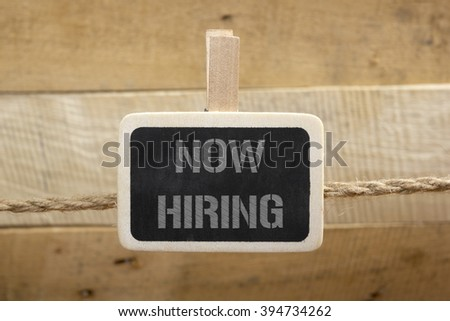 Now hiring handwritten with white chalk on a blackboard at wooden background - stock photo