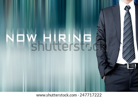 NOW HIRING sign on motion blur abstract background with standing businessman - stock photo