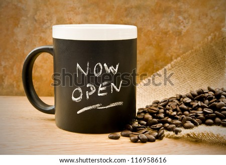 now open, coffee mug with coffee beans & hessian on counter
