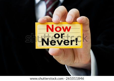 Now or never! written on a card in businessman hand - stock photo