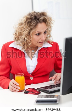 Now that is interesting - businesswoman in the office looking at her computer screen - stock photo