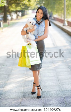 Nowhere without my puppy. Fashionable young woman holding a Maltese dog in her arms and carrying a lots of colorful shopping bags. - stock photo