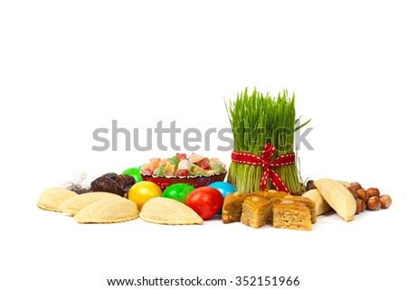 Nowruz in Azerbaijan. Colored eggs for Easter and traditional sweets on white background. Selective focus.
