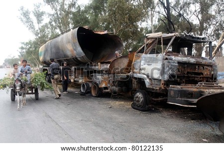 NOWSHERA, PAKISTAN - JUN 28: Unidentified children ride on a donkey-cart pass through a burnt NATO oil-tanker which was destroyed in explosion last night, at Pabbi area on June 28, 2011in Nowshera, Pakistan.