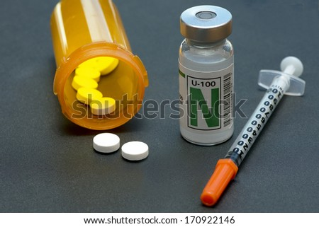 NPH insulin, syringe, and medication for the control of diabetes. - stock photo