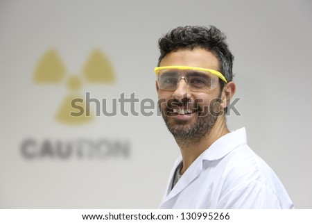 Nuclear plant employee against a wall with caution radioactive symbol - stock photo