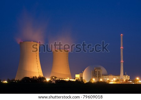 Nuclear power plant at night in Grohnde near Hameln  in Lower Saxony, Germany.  At the left are the cooling towers with water vapor, at the right the reactor. - stock photo