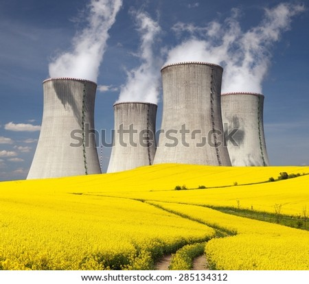 Nuclear power plant Dukovany and golden flowering field of rapeseed with rural road - Czech Republic - two possibility for production of energy - stock photo
