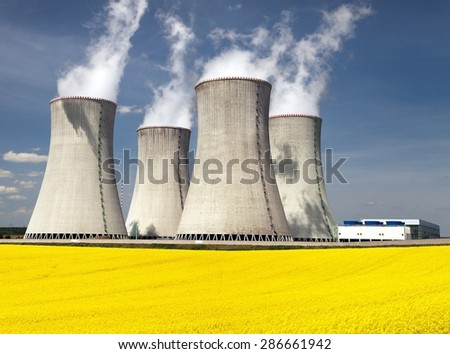 Nuclear power plant Dukovany with golden glowering field of rapeseed - Czech Republic - two possibility for production energy