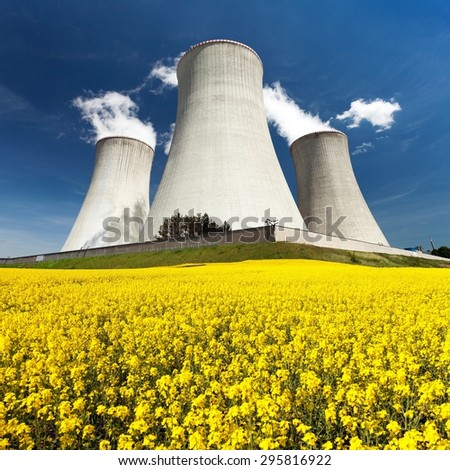 Nuclear power plant Dukovany with golden glowering field of rapeseed - Czech Republic - two possibility for production of energy - stock photo